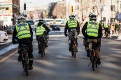 Quattro poliziotti che per mezzo della bici per muoversi veloce e facile immagini stock libere da diritti