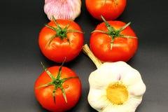 Quattro pomodori maturi succosi rossi e due teste di aglio su un fondo nero immagini stock