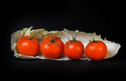 Quattro pomodori su un pezzo di cavolo Fotografia Stock