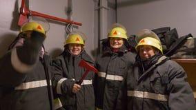 Quattro pompieri sorridenti della donna nella caserma dei pompieri video d archivio