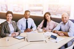 Quattro professionisti di affari che esaminano la macchina fotografica nel corso di una riunione Immagine Stock Libera da Diritti