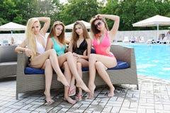 Quattro ragazze in bikini che si siedono sullo strato nei precedenti dello stagno Fotografie Stock