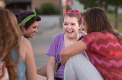 Quattro ragazze teenager che ridono scioccamente fotografia stock