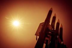 Quattro razzi del sistema missilistico contraereo sono diretti verso l'alto contro un fondo del sole luminoso Immagine tonificata Fotografie Stock Libere da Diritti
