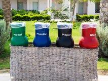 Quattro riciclano i recipienti per la segregazione residua (vetro, carta, metallo e plastica) Ecologia e concetto di riciclaggio immagine stock