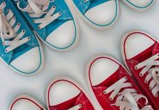 Quattro scarpe da tennis di paia su una superficie di legno bianca Immagine Stock