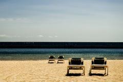 Quattro sedie adagiantesi su una spiaggia (contrasto) Immagini Stock