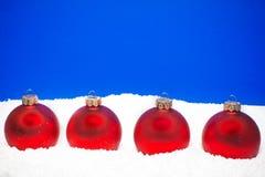 Quattro sfere di natale sulla neve Fotografie Stock