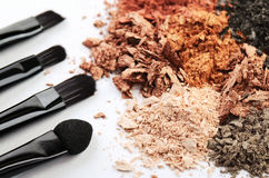 Quattro spazzole di trucco ed ombretti sbriciolati dei colori differenti Fotografie Stock Libere da Diritti