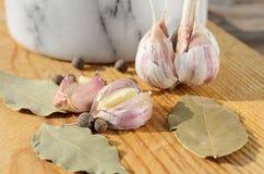 Quattro spezie, aglio e foglia di alloro su un fondo di legno Fotografia Stock