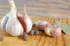 Quattro spezie, aglio e foglia di alloro su un fondo di legno Immagine Stock