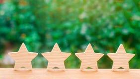 Quattro stelle di legno Il concetto della valutazione e della valutazione La valutazione dell'hotel, ristorante, applicazione mob fotografie stock libere da diritti