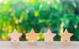 Quattro stelle di legno Il concetto della valutazione e della valutazione La valutazione dell'hotel, ristorante, applicazione mob immagine stock