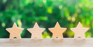 Quattro stelle di legno Il concetto della valutazione e della valutazione La valutazione dell'hotel, ristorante, applicazione mob fotografia stock