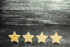 Quattro stelle di legno Il concetto della valutazione e della valutazione La valutazione dell'hotel, ristorante, applicazione mob fotografia stock libera da diritti
