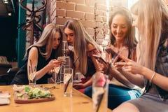 Quattro studentesse sorridenti che si siedono nel self-service che chiacchiera facendo uso dei telefoni cellulari immagini stock libere da diritti