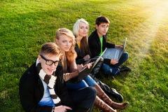 Quattro studenti con il computer portatile Fotografia Stock