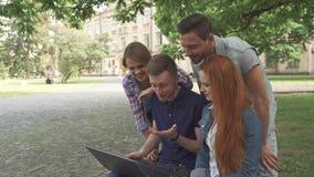 Quattro studenti ridono di che cosa vedono sul computer portatile sulla città universitaria immagini stock libere da diritti