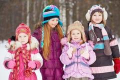 Quattro supporti delle ragazze insieme nel parco di inverno Fotografia Stock