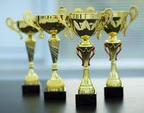 Quattro tazze dell'oro sulla tavola Fotografia Stock