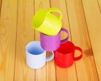 Quattro tazze di plastica di colore differente su fondo di legno leggero Fotografia Stock Libera da Diritti