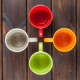 Quattro tazze di tè di colore hanno sistemato in un incrocio, vista superiore Fotografie Stock