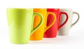 Quattro tazze di tè di colore indicate nella fila Immagine Stock Libera da Diritti