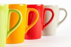 Quattro tazze di tè di colore indicate nella fila Fotografia Stock