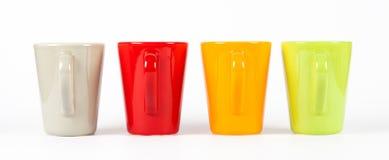 Quattro tazze di tè di colore indicate in una fila Immagini Stock