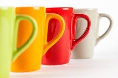 Quattro tazze di tè di colore indicate in una fila Fotografia Stock Libera da Diritti