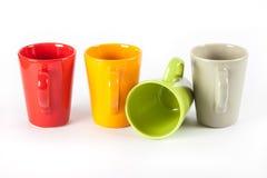 Quattro tazze di tè di colore indicate in una fila Fotografia Stock