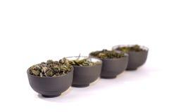 Quattro tazze di tè di erbe. Immagini Stock
