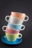 Quattro tazze di tè impilate sul nero Immagini Stock