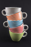 Quattro tazze di tè impilate sul nero Immagine Stock Libera da Diritti