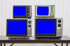 Quattro televisioni d'annata con gli schermi blu di chiave di intensità immagine stock libera da diritti