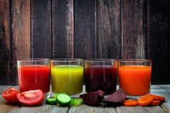 Quattro tipi di succhi di verdura sani con un vecchio fondo di legno Immagine Stock