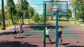 Quattro uomini adatti che giocano pallacanestro sul campo sportivo nella via di estate video d archivio