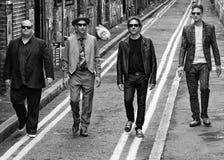 Quattro uomini che camminano giù la strada Fotografia Stock