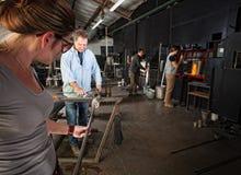 Lavoratori che fanno gli oggetti di vetro immagine stock