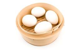 Quattro uova bianche in cestino di bambù immagini stock