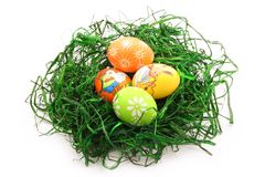 Quattro uova di Pasqua in un nido isolato su bianco immagine stock libera da diritti