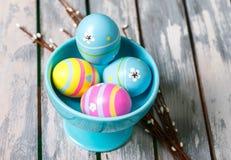Quattro uova di Pasqua in una tazza Fotografia Stock Libera da Diritti