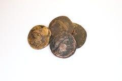Quattro vecchie monete con i ritratti degli imperatori su un fondo bianco Immagine Stock
