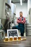 Quattro vetri della birra del mestiere sul vassoio e sul fabbricante di birra del campionatore della birra che stanno nel fondo Immagine Stock Libera da Diritti