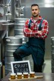 Quattro vetri della birra del mestiere sul vassoio e sul fabbricante di birra del campionatore della birra che stanno nel fondo Fotografie Stock