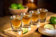 Quattro vetri di colpo con la bottiglia di tequila e la ciotola di calce con sale ad una barra Fotografia Stock Libera da Diritti