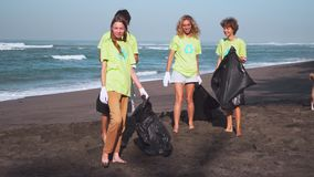 Quattro volontari in magliette verdi con l'immagine riciclano raccolgono l'immondizia sulla spiaggia, considerante la macchina fo stock footage