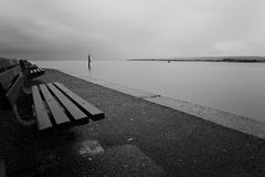 Quay Bench. A bench on a quay against still, flat water on a stormy day Royalty Free Stock Photography