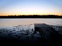 Quay dans le lac au coucher du soleil Photographie stock libre de droits