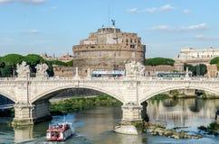 Quay des Flusses Tiber in Rom, eine Brücke und eine Gruppe ausländische Touristen auf einem Bootsausflug und Architekturmonumente Lizenzfreie Stockfotografie